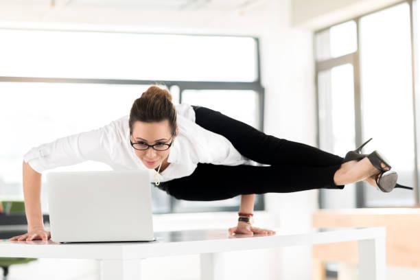 lächelnde flexible frau gerade am laptop - yoga fürs büro stock-fotos und bilder