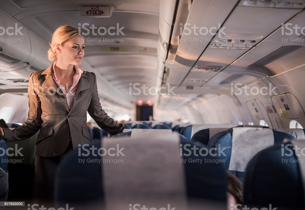 Smiling flight attendant on duty in the airplane. stock photo