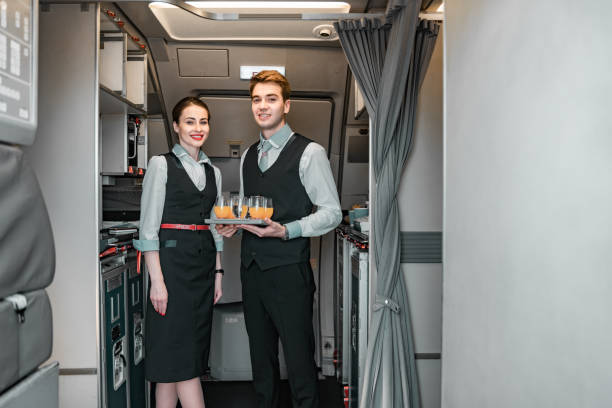 Smiling flight attendant with pilot posing for camera Caucasian stewardess standing with her colleague near door of airliner stock photo. Airways concept cabin crew stock pictures, royalty-free photos & images