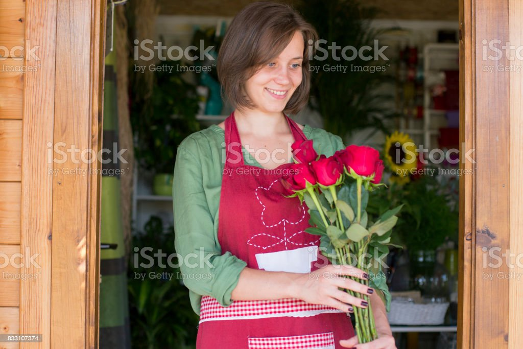 Young florist with red roses standing in flower shop doorway, wearing...