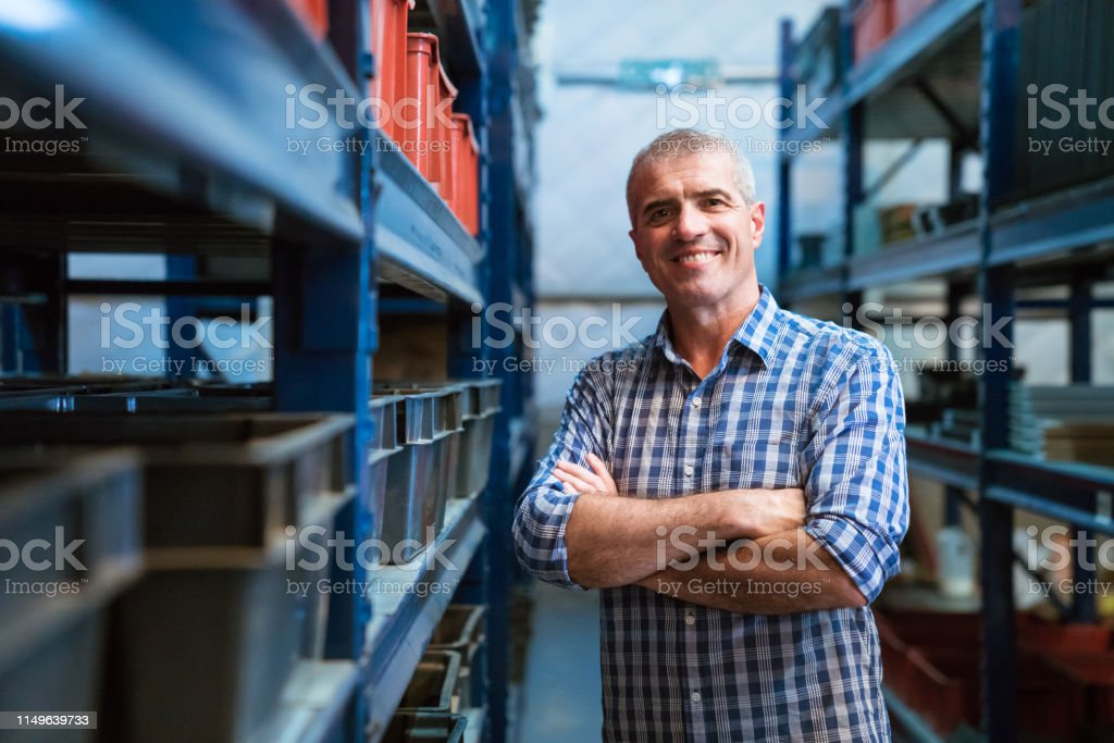 Smiling foreman with arms crossed in warehouse Portrait of smiling mature foreman with arms crossed in warehouse. Factory manager is wearing shirt. He is standing in storage room. 55-59 Years Stock Photo