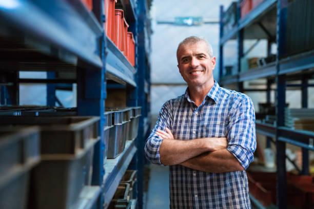 lachende voorman met armen gekruist in magazijn - warehouse worker stockfoto's en -beelden