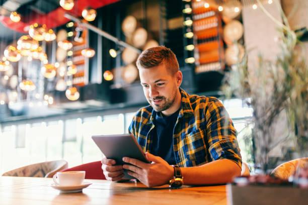 프리랜서 일을 위해 태블릿을 사용 하 여 미소. 앞 테이블 커피 한잔에 그. 식당 인테리어입니다. - 디지털 태블릿 사용하기 뉴스 사진 이미지