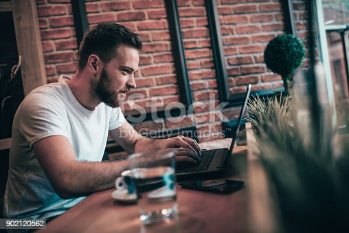 istock Smiling Freelancer Working at his Favorite Coffee Place 902120562