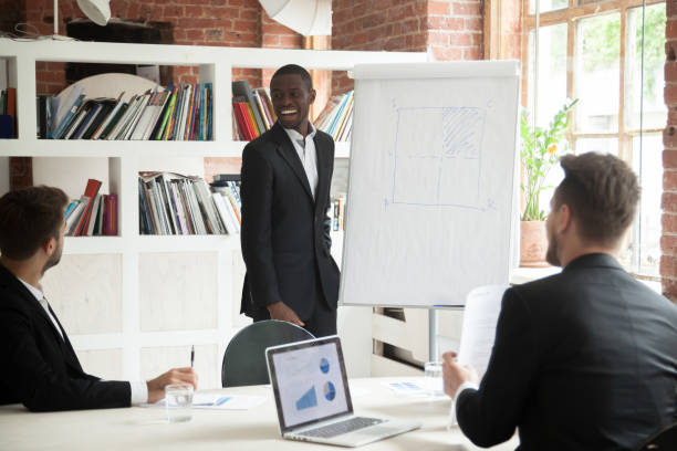 smiling friendly african coach giving presentation to businessmen in office - project manager stock photos and pictures