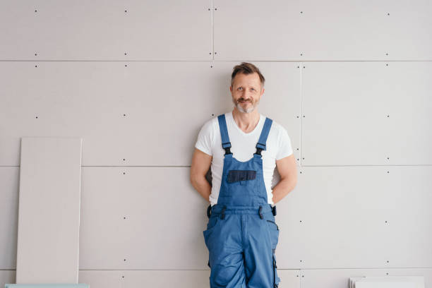 Smiling friendly handyman in denim overalls stock photo
