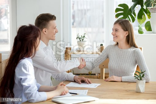 istock Smiling friendly hr manager handshaking applicant welcoming at job interview 1127950074
