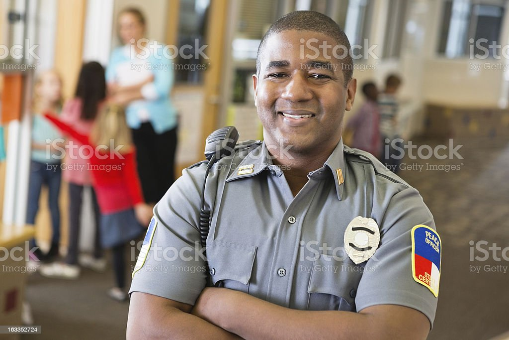 Smiling friendly police officer providing security on school campus stock photo