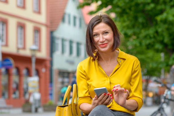 Smiling friendly woman using a mobile in town stock photo