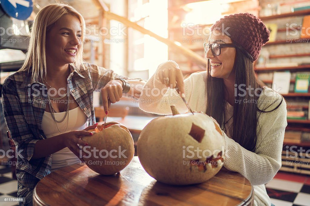 Smiling friends communicating while carving pumpkins for Halloween. stock photo