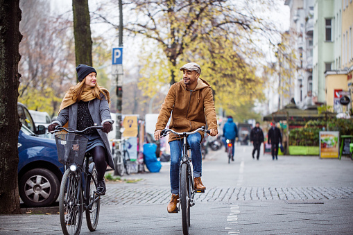 Smiling friends cycling on street. Man and woman are in warm clothing. They are commuting in city.