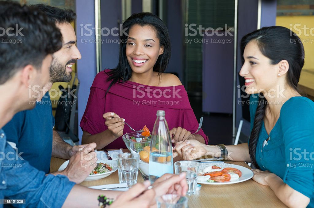 Smiling friends eating together stock photo