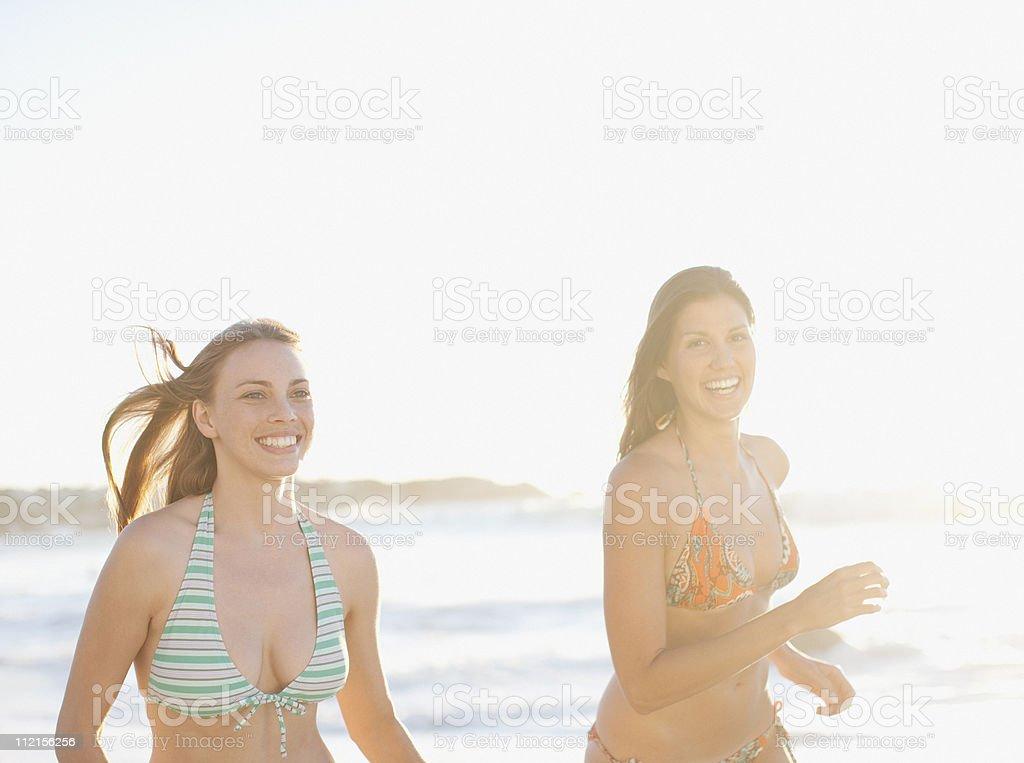 Smiling friends in bikinis running on beach royalty-free stock photo