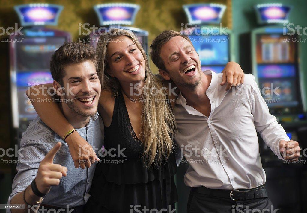 Smiling Friends in Casino Winning on Slot Machine. stock photo
