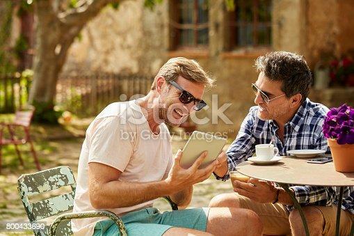 istock Smiling friends looking at digital tablet in yard 800433690