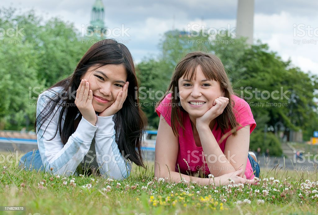 smiling friends lying on grass royalty-free stock photo