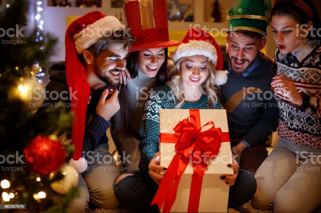 lächelnden Freunde öffnen Magie Weihnachtsgeschenk – Foto