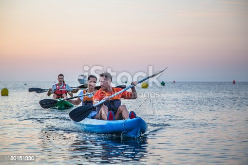 Middle-aged Caucasian couples enjoying paddling kayaks at sunrise in Mediterranean Sea off coast of Spain.