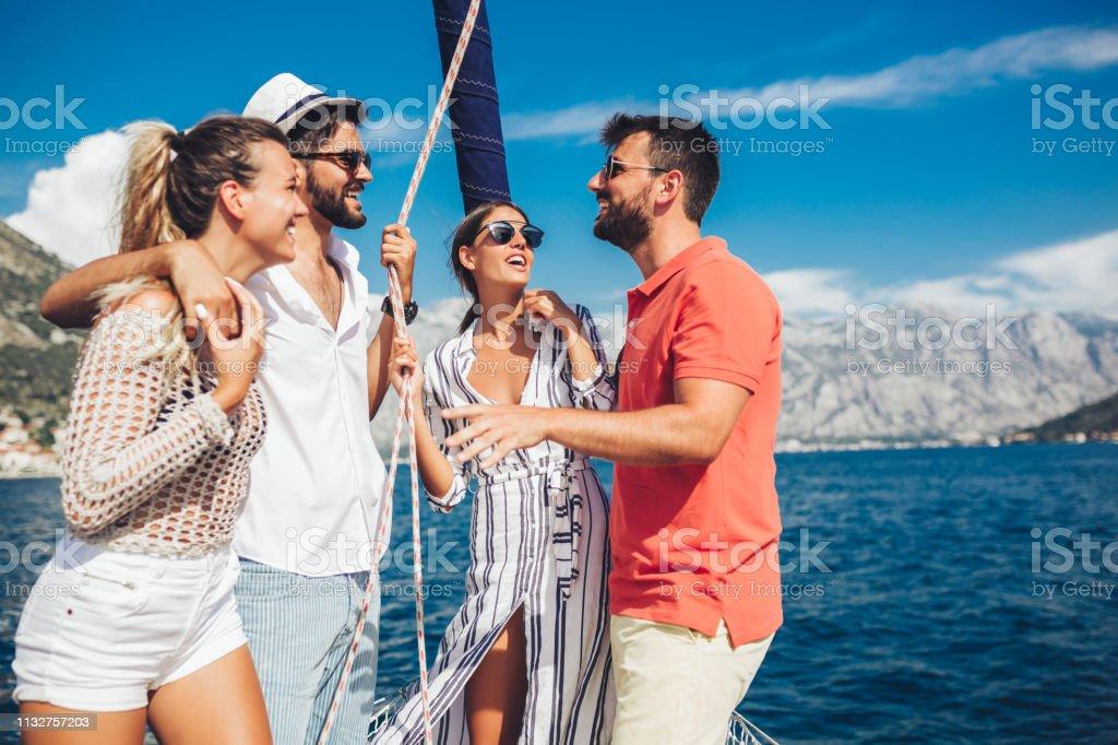 Amigos sonriendo navegando en yate. Concepto de vacaciones, viajes, mar, amistad y personas - foto de stock