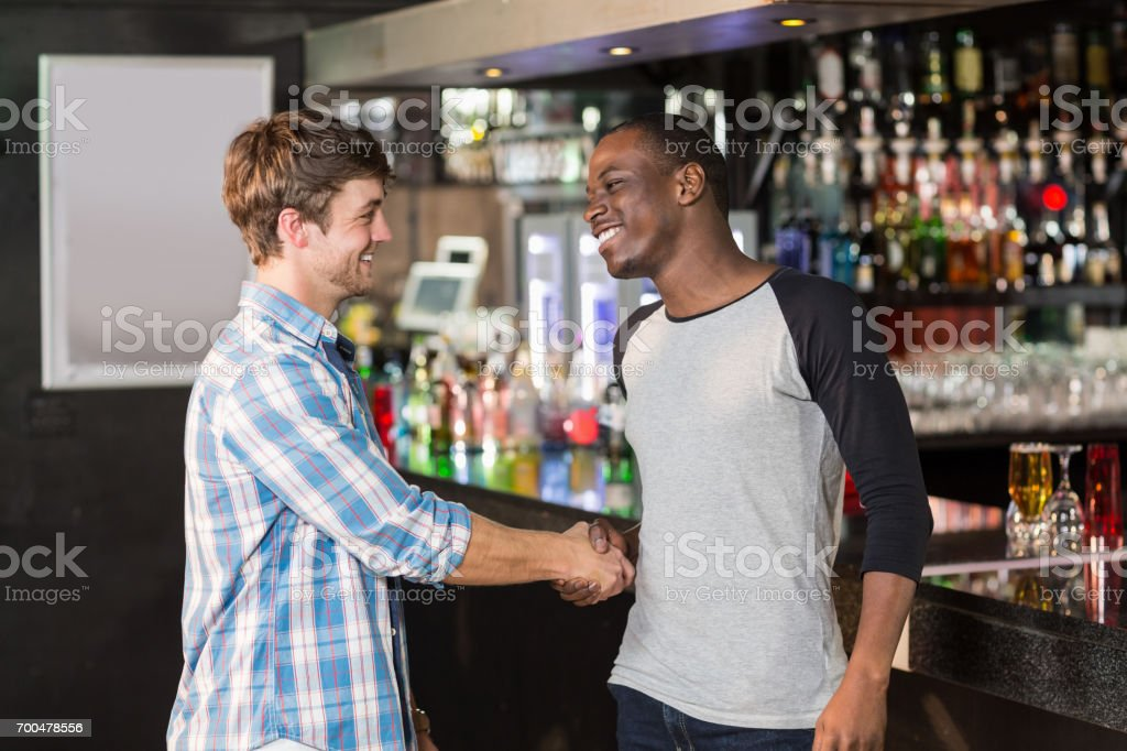 Smiling friends shaking hands stock photo