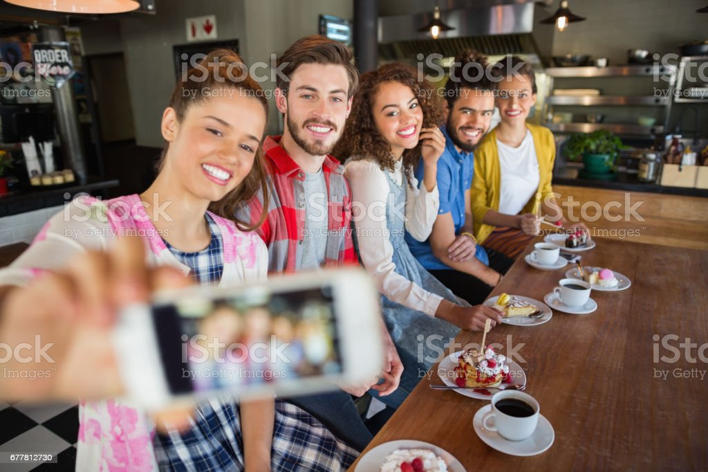 Smiling friends taking photo in pub royalty-free stock photo