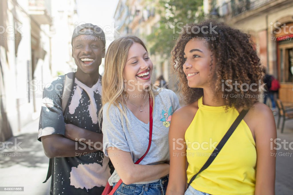 Smiling friends talking while standing in city stock photo