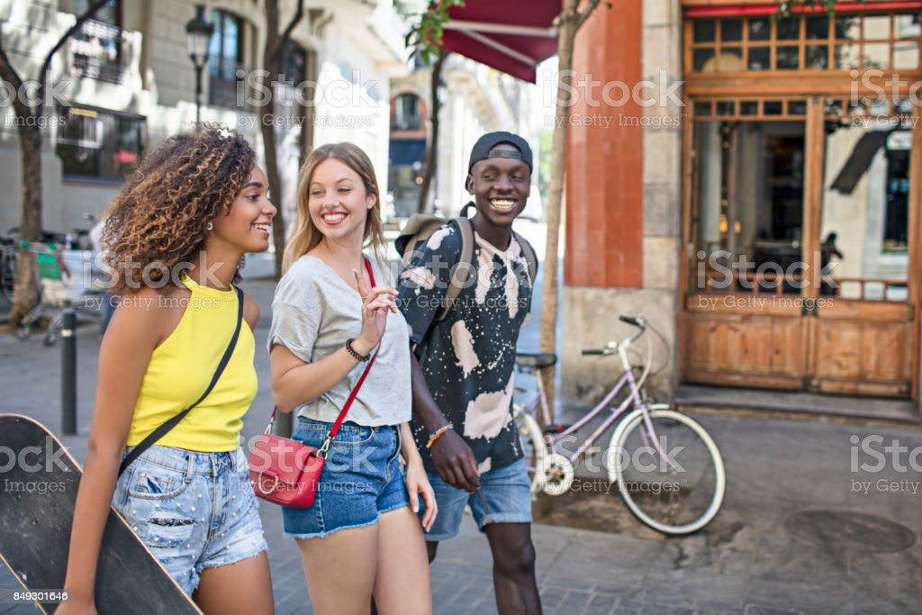 Smiling friends talking while walking in city stock photo