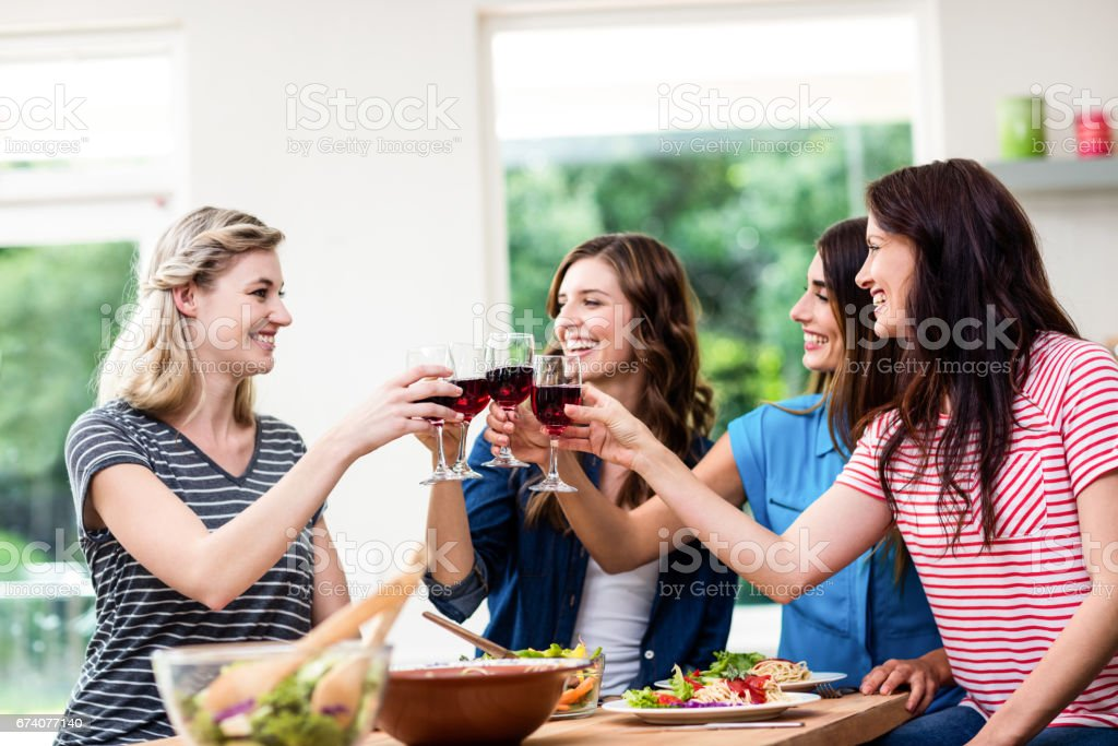 Smiling friends toasting red wine glasses stock photo