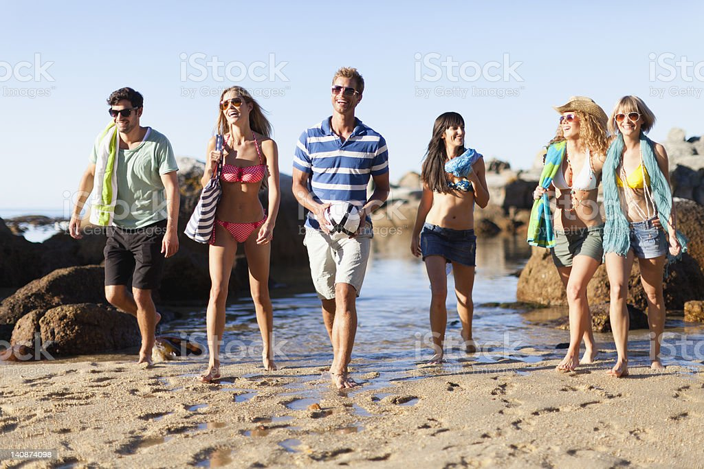 Smiling friends walking on beach stock photo