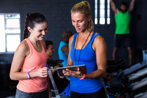 amigos sonrientes con tableta digital en gimnasio - entrenador personal fotografías e imágenes de stock