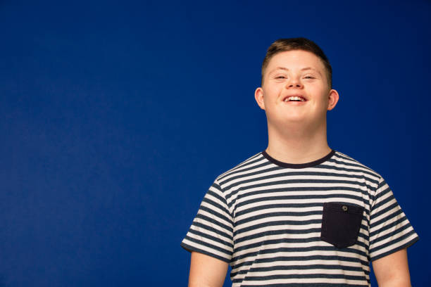 Smiling From Ear to Ear A teenage Down syndrome boy looking at the camera, smiling and looking happy. persons with disabilities stock pictures, royalty-free photos & images