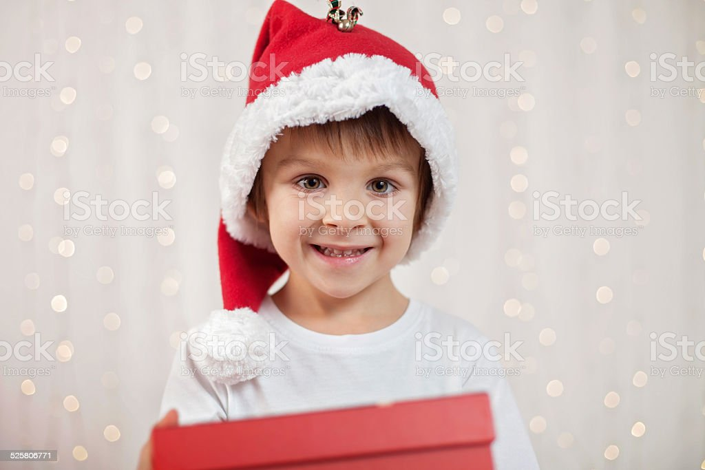 5f69830502519 Smiling funny child in Santa red hat holding Christmas gift royalty-free  stock photo