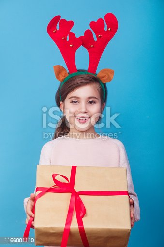istock Smiling funny child with reindeer antlers holding Christmas gift in hand. Christmas concept. 1166001110