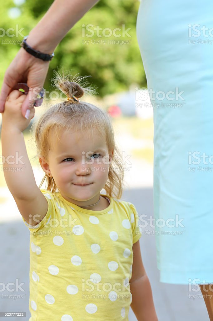 Smiling funny little girl outdoor holding mother hand portrait. Woman...