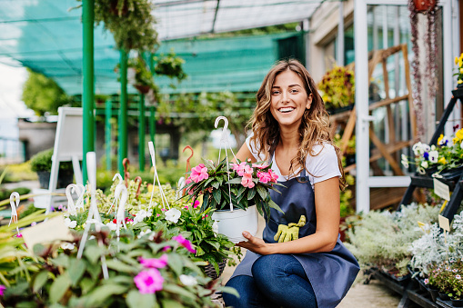 Attractive young woman working in a garden center.