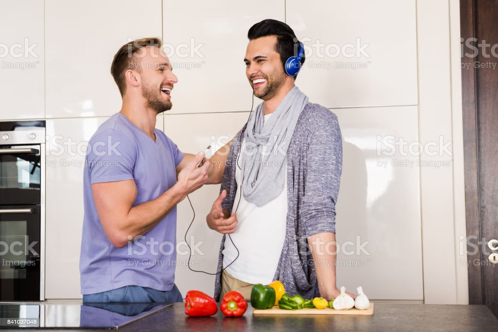 Smiling gay couple listening to music stock photo
