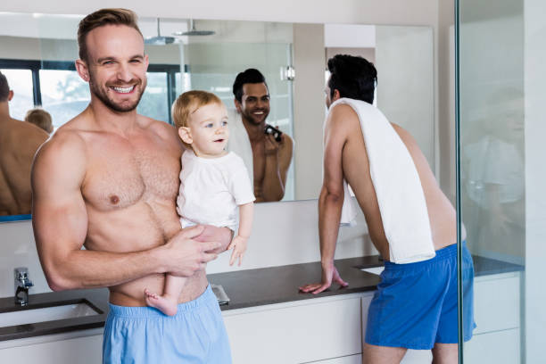 Smiling gay couple with child stock photo