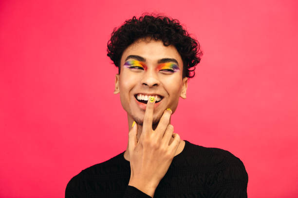 Smiling gay man with rainbow eye shadow and smiley nailpaint stock photo