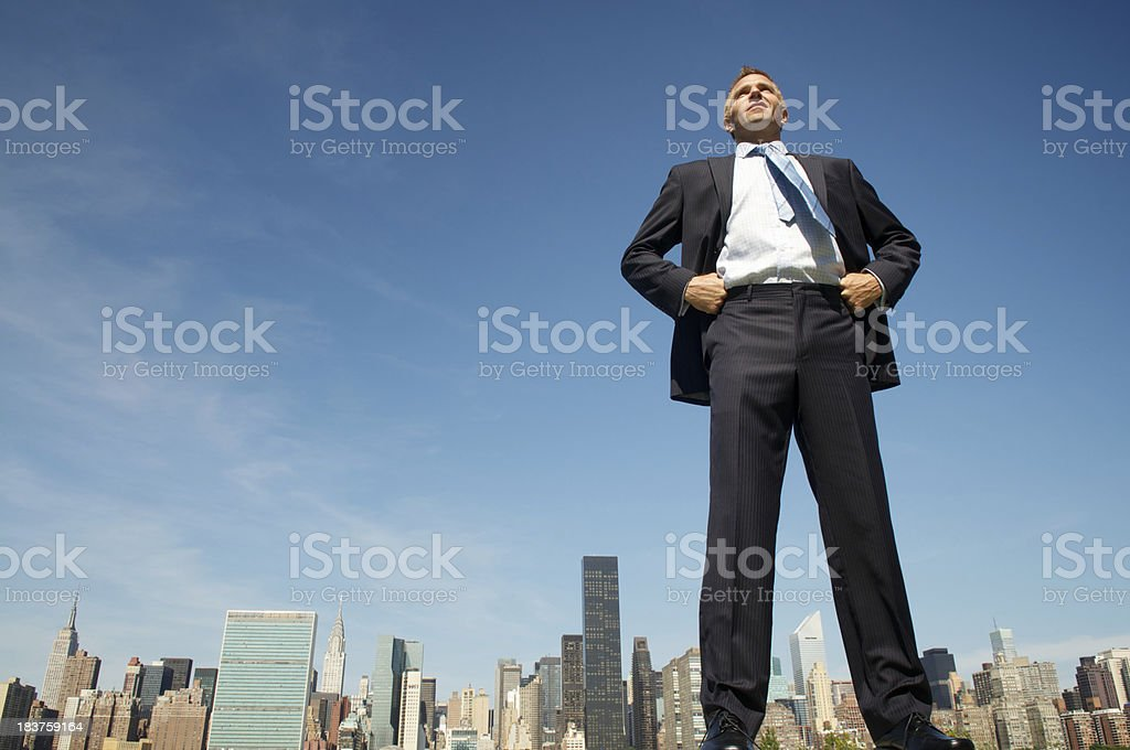 Smiling Giant Businessman Standing Tall and Proud Above City Skyline stock photo
