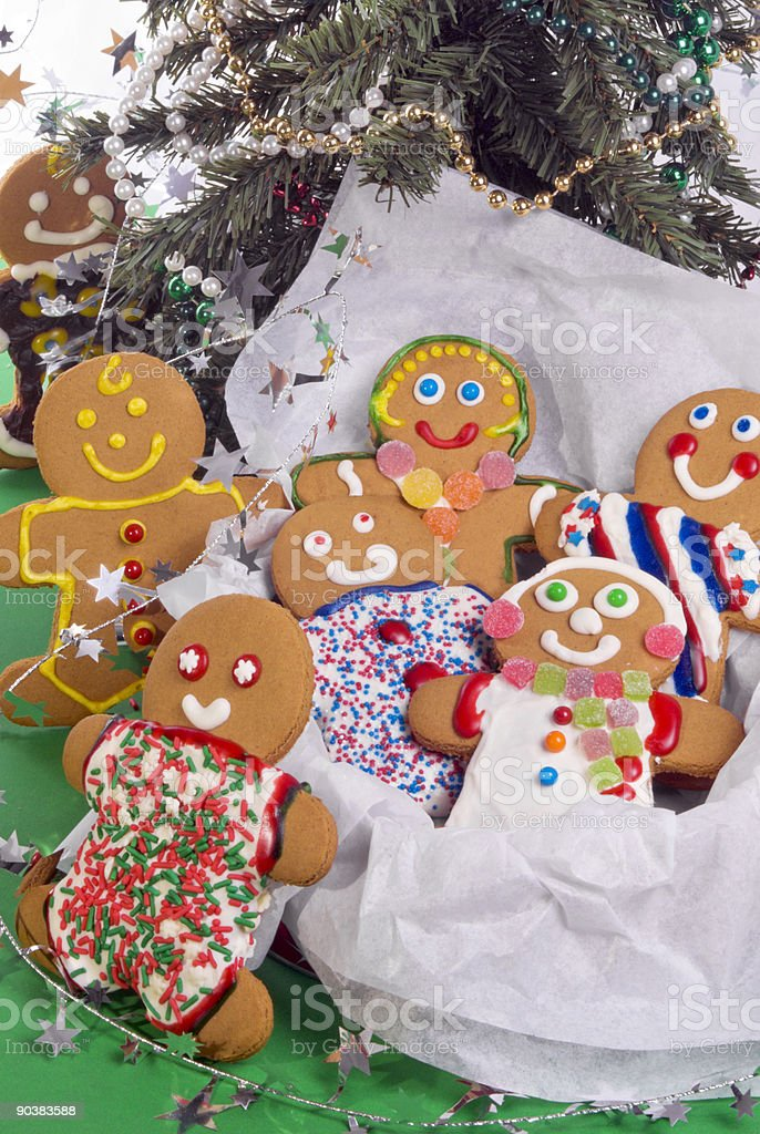 Smiling gingerbread man and his family under a Christmas tree royalty-free stock photo