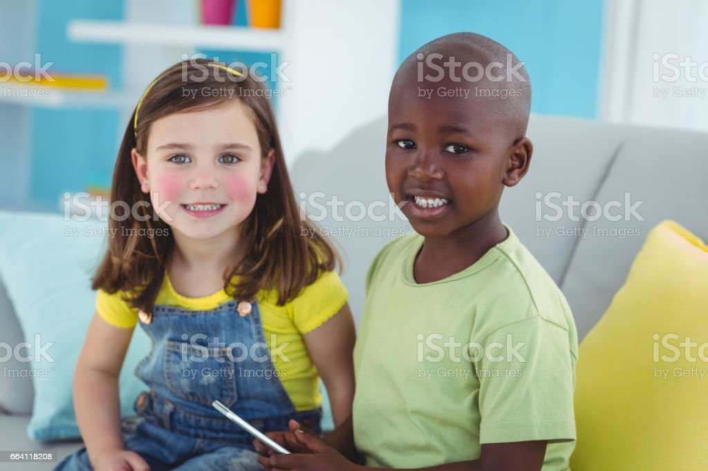 Smiling girl and boy using smartphone foto stock royalty-free