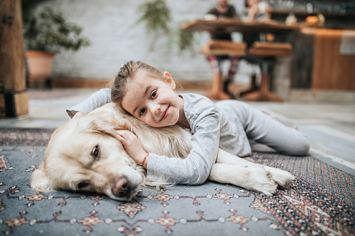 Smiling girl and her golden retriever on carpet at home.