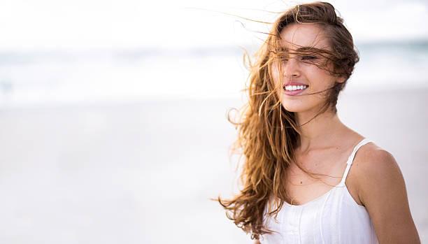 lächelnd mädchen am strand mit textfreiraum - haare ohne lockenstab wellen stock-fotos und bilder