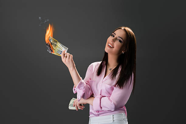 Smiling girl burns money. Concept of extravagance – Foto