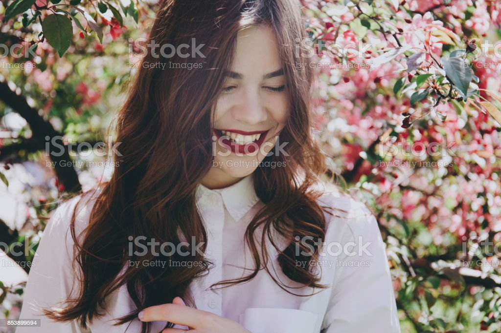 Smiling girl by the blossoming tree. stock photo