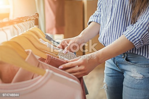 Unrecognizable woman choosing clothes on rack in showroom. Sale, fashion and consumerism concept, crop