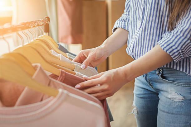 uśmiechnięta dziewczyna bying ubrania w salonie - odzież zdjęcia i obrazy z banku zdjęć
