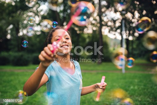 Girl having fun with soap bubbles at the park