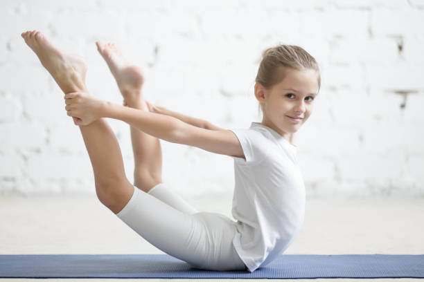 Smiling girl child in dhanurasana pose, white studio background stock photo