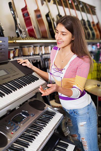 smiling  girl choosing synthesizer - klavier verkaufen stock-fotos und bilder